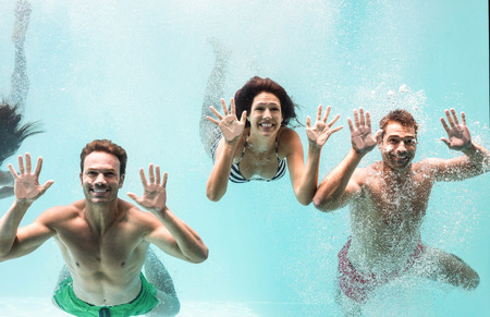 loving couple: Two couples enjoying and swimming underwater in swimming pool Stock Photo