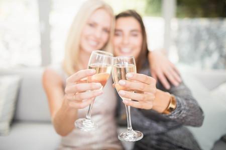 Schöne Frauen lächelnd und Champagnerflöte Toasten