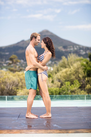 each other: Young couple cuddling each other near pool on a sunny day Stock Photo
