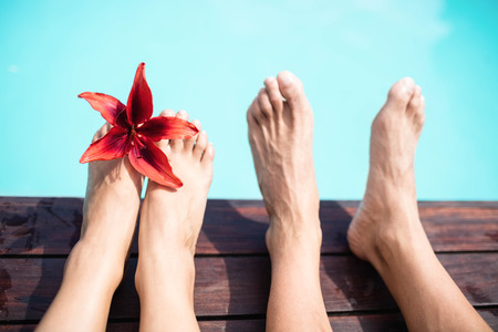bare feet: Close-up of couple bare feet against swimming pool on a sunny day