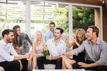 popping: Man popping champagne bottle while celebrating with friends Stock Photo
