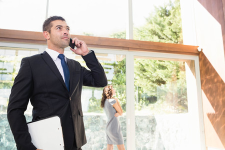 realestate: Real-estate agent talking on the mobile phone and client looking at the apartment