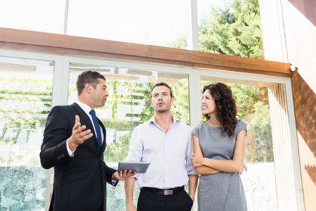 realestate: Young couple meeting real-estate showing a house project on a digital tablet Stock Photo