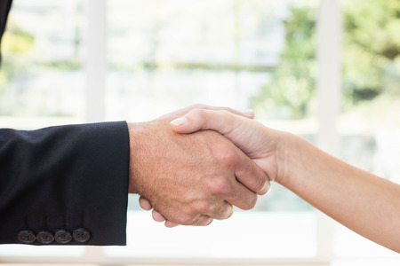 realestate: Real-estate agent shaking hands with client after the deal