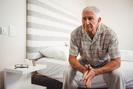 Senior man sitting on bed in bedroom Stock Photo