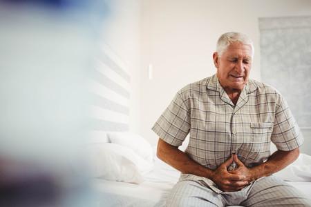 Zieke senior man die lijden aan maagpijn die zijn maag in slaapkamer