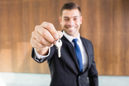 property owners: Real-estate agent giving keys to new property owners Stock Photo