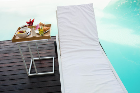 side table: Tray with breakfast in side table and sun lounger near poolside Stock Photo