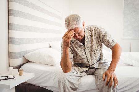 irate: Frustrated senior man sitting on bed in bedroom