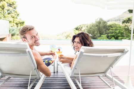 loungers: Young couple sitting on sun loungers by swimming pool Stock Photo