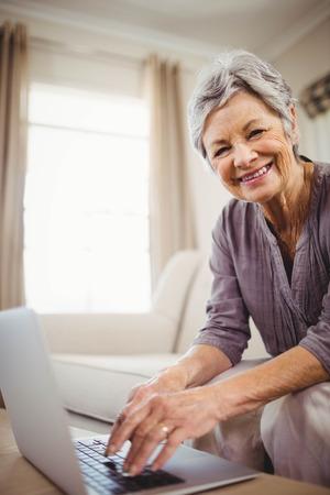 señora mayor: Retrato de la mujer mayor que se sienta en el sofá y sonriendo mientras se utiliza portátil en la sala de estar