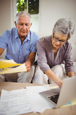 paying bills online: Senior woman sitting with man on sofa and paying bills online on laptop in living room