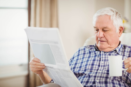 Senior man having a cup of coffee and reading newspaper in living room