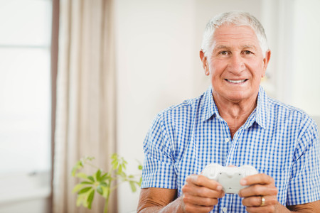 xbox: Senior man with joystick looking at camera and smiling in living room