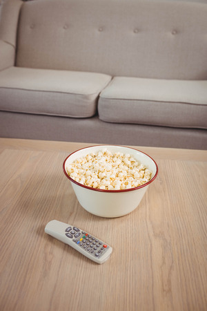 television remote: Bowl of popcorn and television remote on table in living room Stock Photo