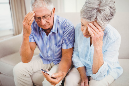 Sad senior couple sitting on sofa and looking at mobile phone in living room