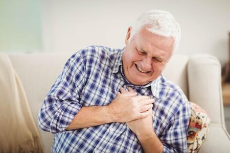 dolor de pecho: Hombre mayor que consigue dolor en el pecho en la sala de estar