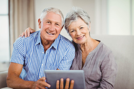 Portrait of senior couple holding digital tablet and smiling while sitting on sofa in living room Stock Photo