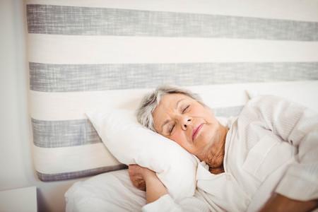 Senior woman sleeping on bed in bedroom