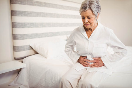 Senior vrouw die lijdt aan buikpijn zittend op bed in de slaapkamer