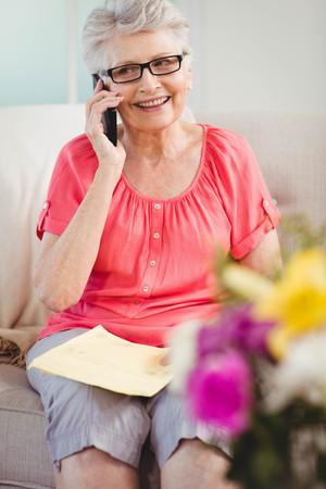 Senior woman talking on phone in living room