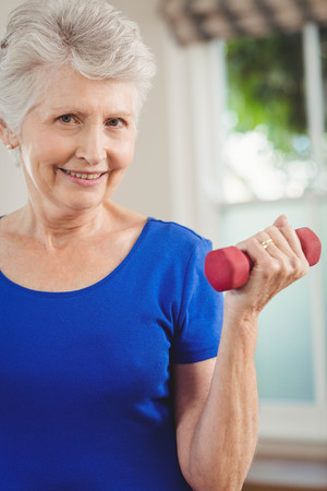 senior woman exercising: Portrait of senior woman exercising with dumbbells at home Stock Photo