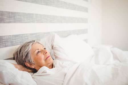 woman in suit: Thoughtful senior woman relaxing on bed