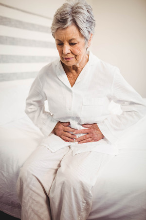 seniors suffering painful illness: Senior woman suffering from stomach ache sitting on bed in bedroom