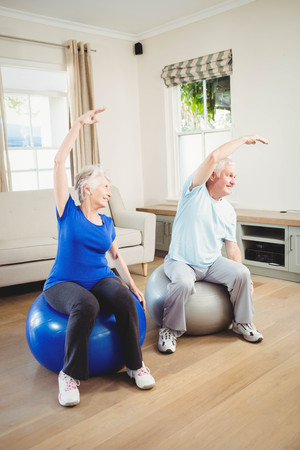 ball stretching: Senior couple doing stretching exercise on exercise ball at home