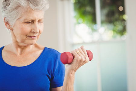 senior woman exercising: Senior woman exercising with dumbbells at home