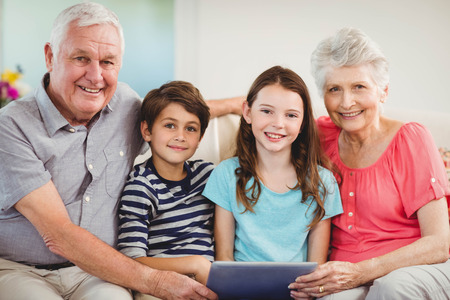 grand father: Portrait of senior couple and their grand children using digital tablet in living room
