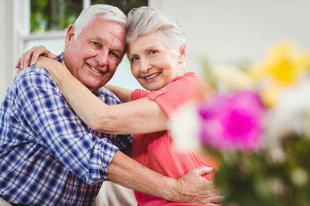 Portrait of senior couple embracing each other in living room Stock Photo