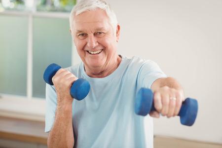 Ritratto di uomo anziano esercitando con manubri a casa