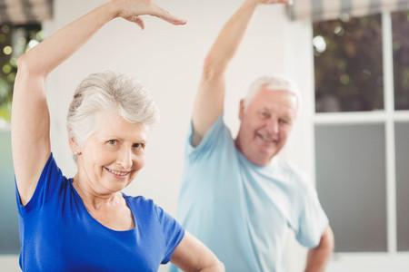 estiramiento: Retrato de pareja de ancianos que realizan ejercicios de estiramiento en el hogar Foto de archivo