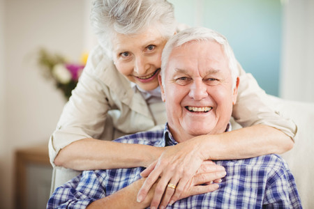 man woman hugging: Portrait of senior woman embracing man in living room Stock Photo