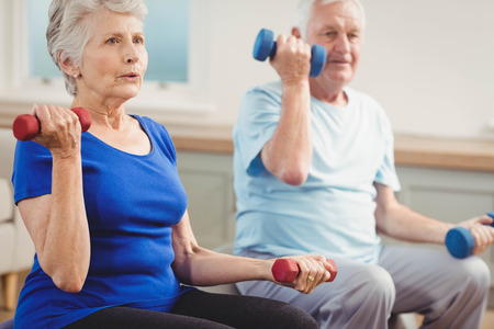 senior citizens: Senior couple lifting dumbbells while sitting on exercise ball at home