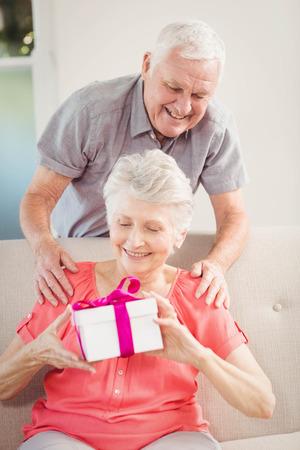 Senior man smiling while giving a surprise gift to senior woman