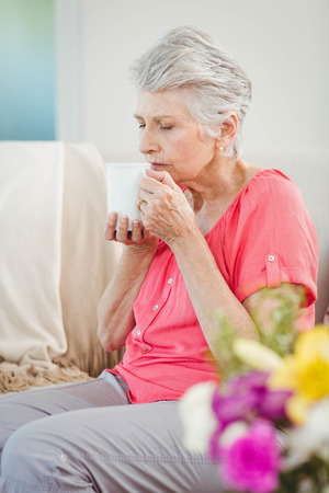 sensory perception: Senior woman smelling a cup of coffee at home