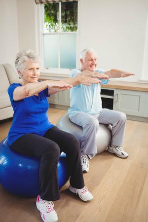 exercise ball: Senior couple exercising on exercise ball at home