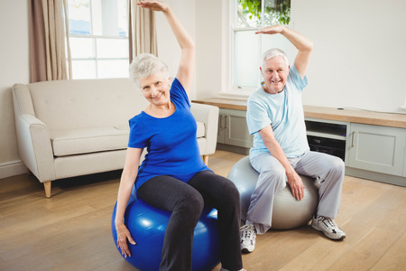 Senior couple doing stretching exercise on exercise ball at home