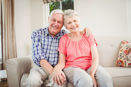 Portrait of senior couple sitting on sofa and smiling in living room