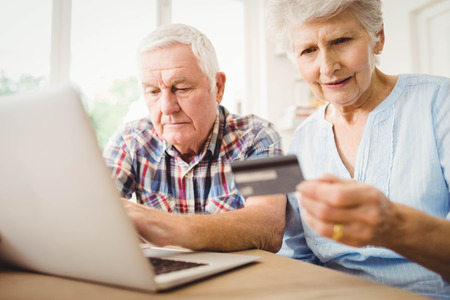 paying bills online: Senior couple paying bills online on laptop