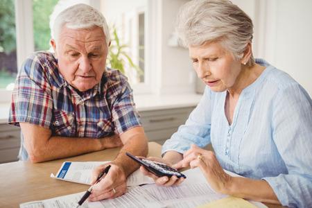 Worried senior couple checking their bills at home 版權商用圖片 - 52773943