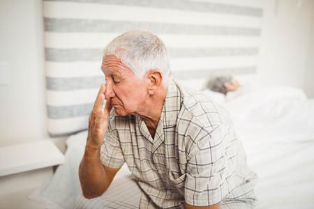 glum: Senior man sitting on bed in bedroom Stock Photo