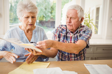 figuring: Worried senior couple discussing their bills at home