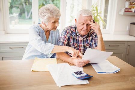 Besorgt Senior Paar, ihre Rechnungen zu Hause überprüfen