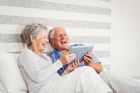 parejas: Pares mayores que ríen mientras que usa la tableta digital en el dormitorio