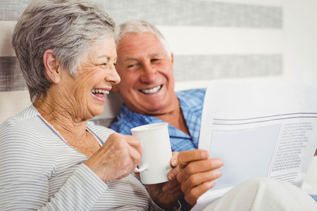 domestic: Senior couple laughing while reading newspaper in bedroom