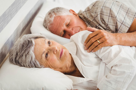 glum: Senior man sleeping while woman still awake on bed in bed room Stock Photo