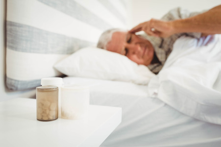 side table: Pillboxes kept on a side table near bed and frustrated senior man in background Stock Photo
